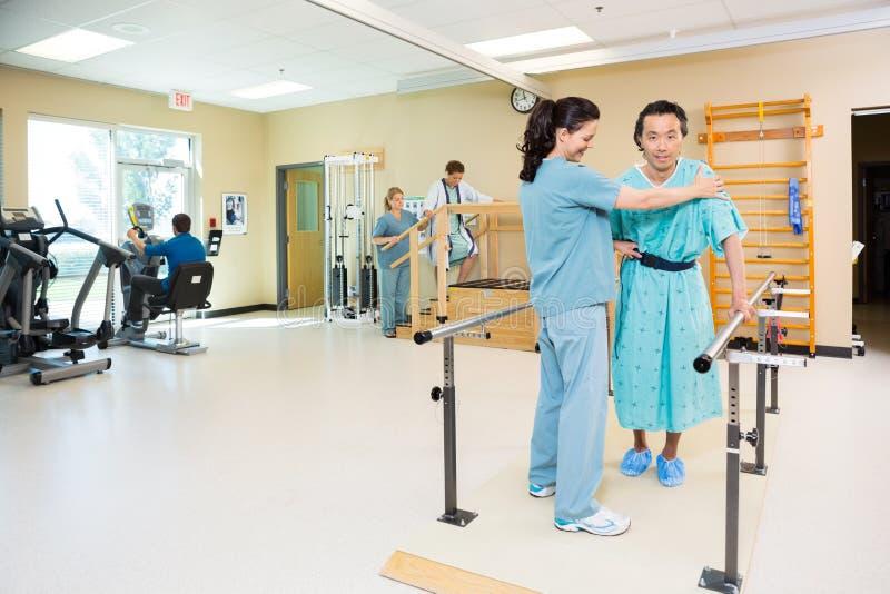 Терапевты помогая пациентам в спортзале больницы стоковая фотография rf