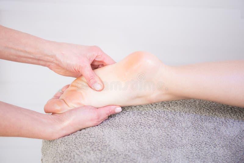Терапевт вручает массажировать женский массаж ноги в салоне курорта стоковые фото
