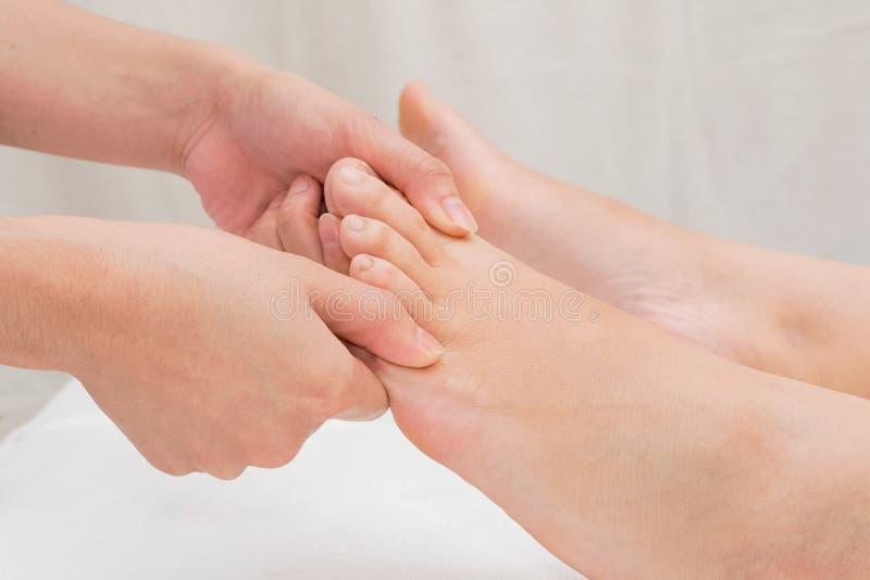 Терапевт делая массаж reflexology на ноге женщины стоковые фото
