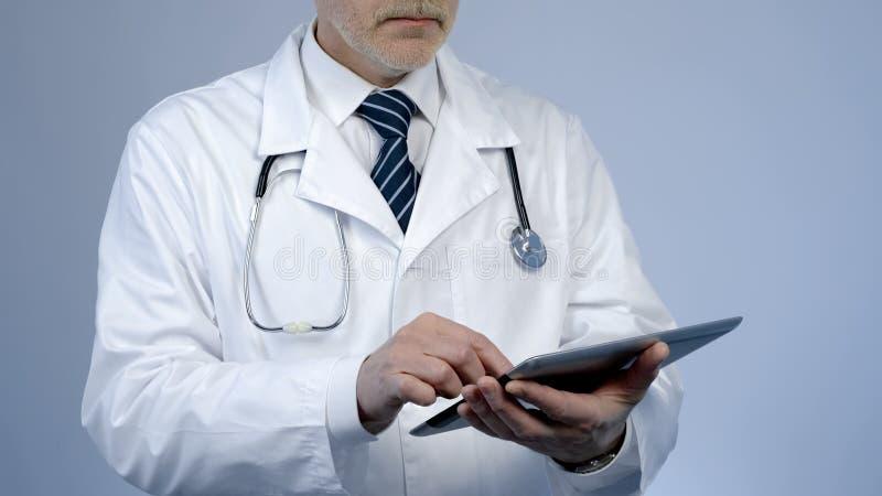 Терапевт используя ПК таблетки для того чтобы проверить результаты теста медицинской истории или лаборатории пациентов стоковые изображения rf