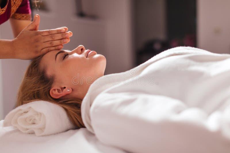 Терапевт касаясь голове его клиента с ладонями стоковые изображения