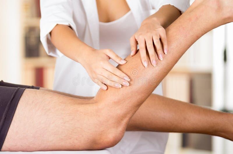 Терапевт крупного плана женский physio вручает работу на мужских ногах пациентов, расплывчатую предпосылку клиники стоковые фотографии rf