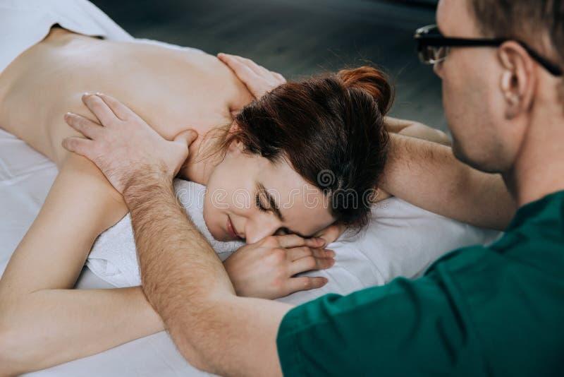 Терапевт массажа делая massager плеча молодой женщины Красивая расслабленная сторона молодой женщины с каштановыми волосами стоковое изображение rf