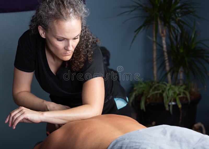 Терапевт массажа используя ее локоть стоковые изображения