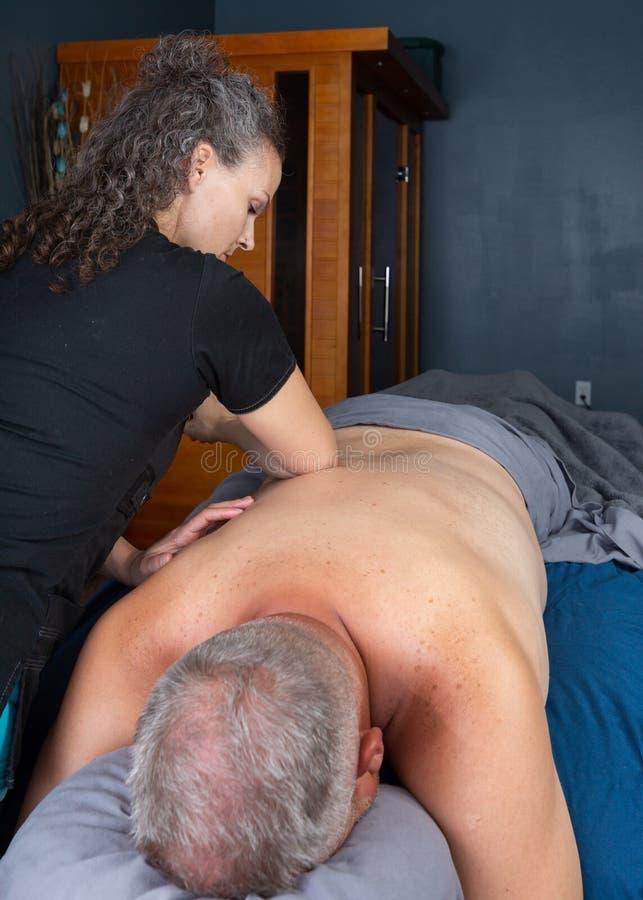 Терапевт массажа используя массаж локтя на мужском клиенте стоковое фото rf