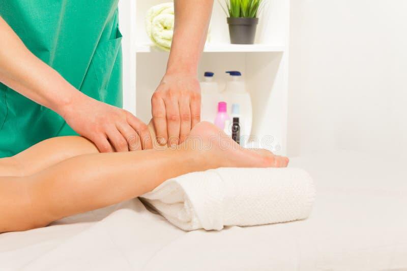 Терапевт массажа массажируя ногу мальчика на шкафе стоковые изображения