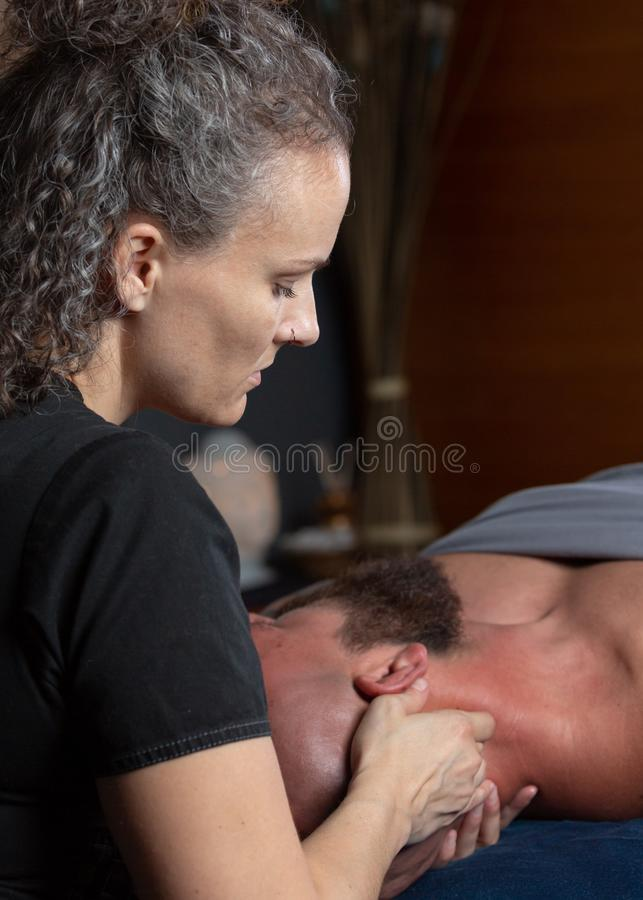 Терапевт массажа работая на шеи пациента стоковое фото rf