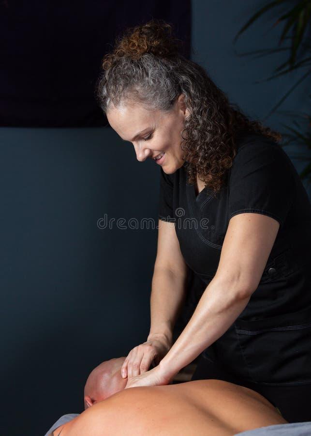 Терапевт массажа работая на шеи пациента стоковые фотографии rf