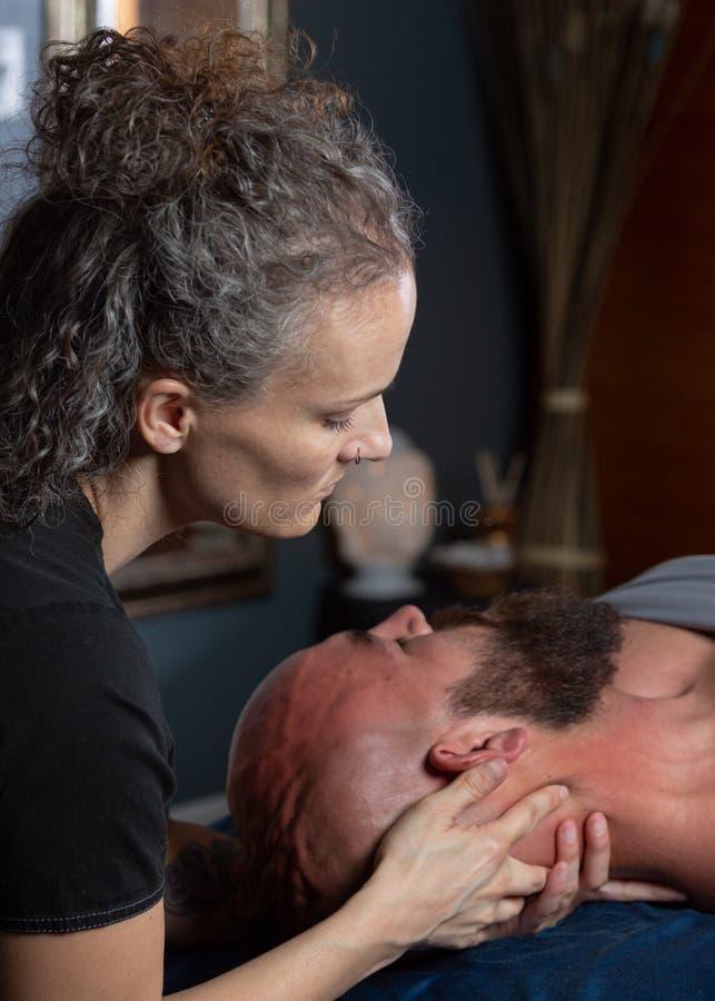 Терапевт массажа работая на шеи человека стоковые фото
