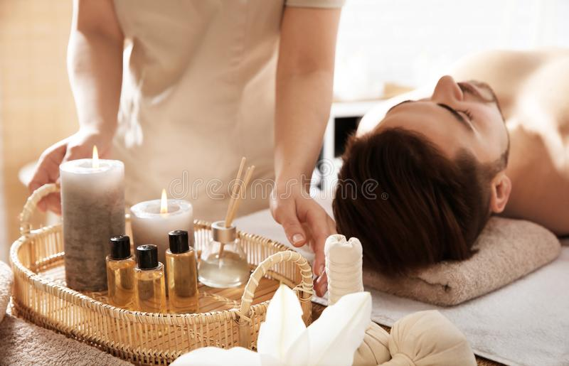 Терапевт массажа с предметами первой необходимости спа и молодой человек стоковое фото rf