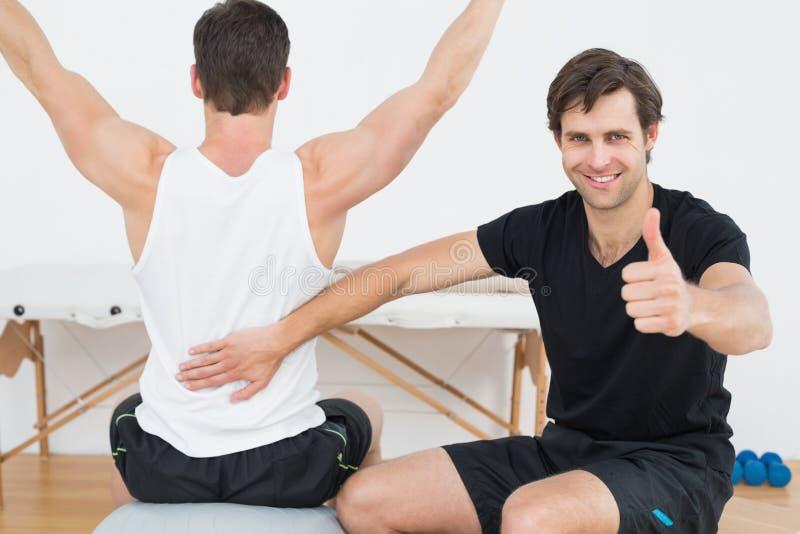 Терапевт показывать большие пальцы руки вверх кроме человека на шарике йоги стоковое изображение