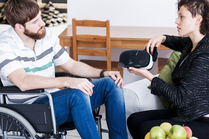 Терапевт показывая изумлённые взгляды VR к пациенту стоковое изображение