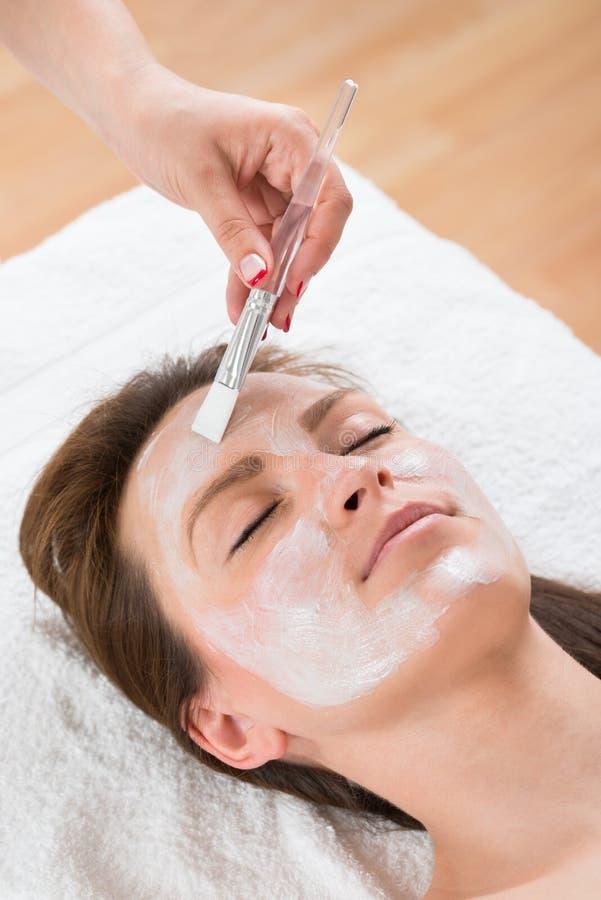 Терапевт прикладывая лицевой щиток гермошлема к женщине стоковое изображение rf