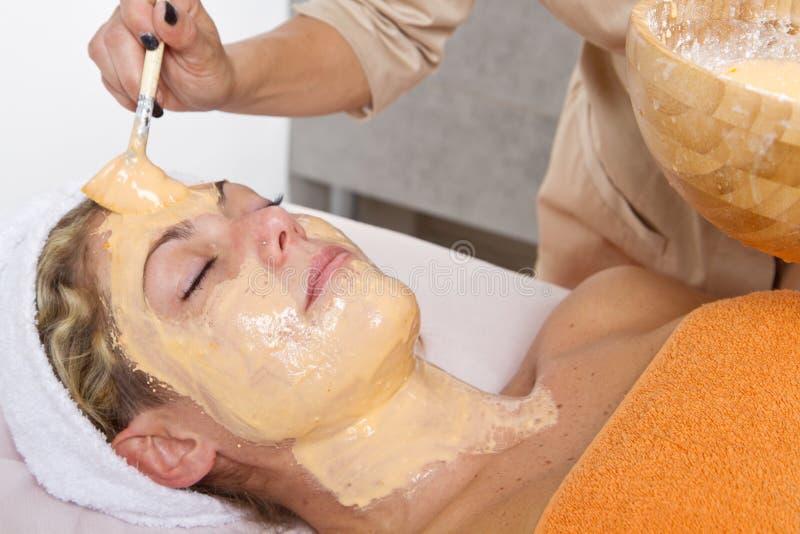 Терапевт прикладывая лицевой щиток гермошлема к красивой молодой женщине в s стоковые изображения rf