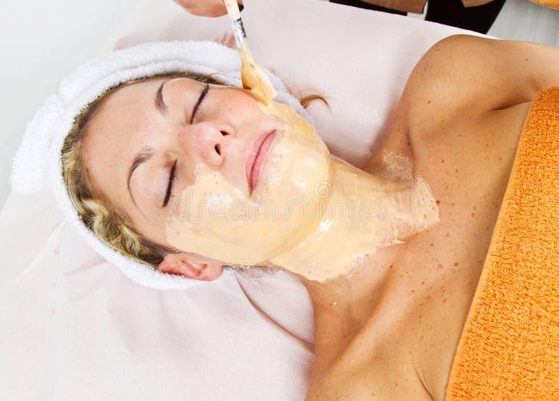 Терапевт прикладывая лицевой щиток гермошлема к красивой молодой женщине стоковая фотография