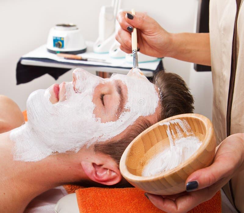 Терапевт прикладывая лицевой щиток гермошлема к красивому курорту younga стоковое изображение