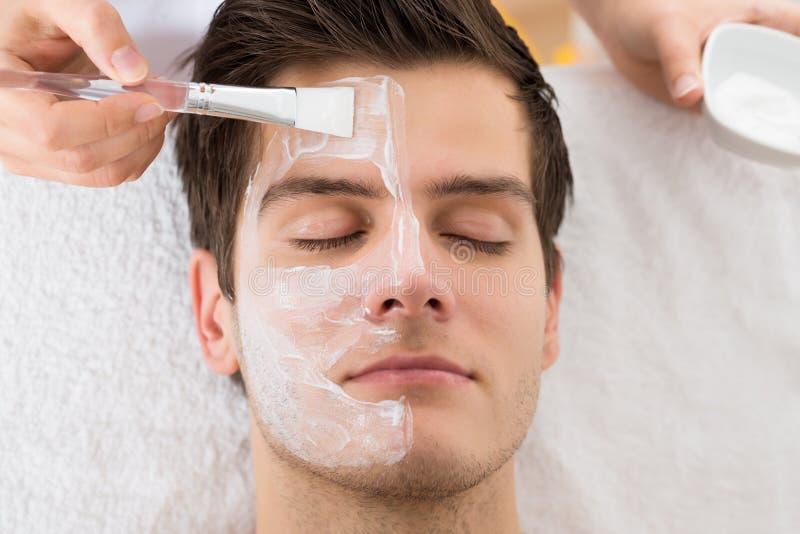 Терапевт прикладывая лицевой щиток гермошлема к человеку стоковые изображения rf