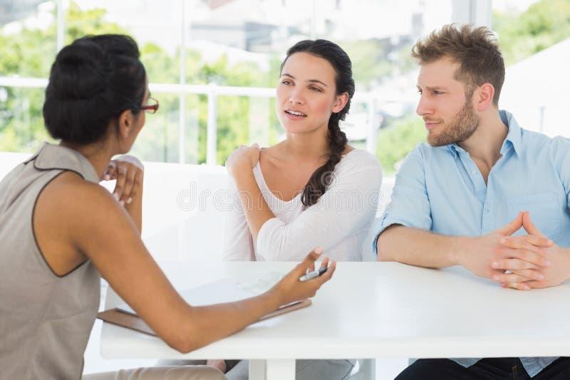 Терапевт разговаривая при пары сидя на столе стоковые фотографии rf