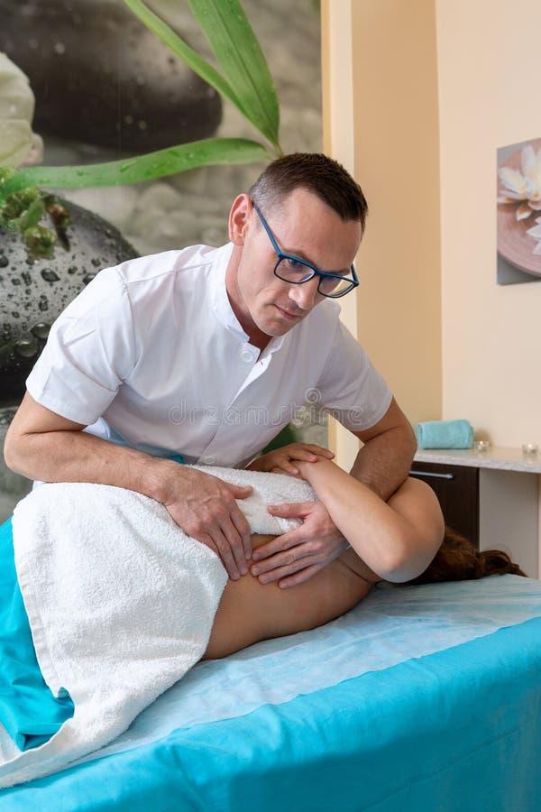 Терапевт Osteopath, делает манипуляцию и массажирует пациента с ушибом стоковые фото