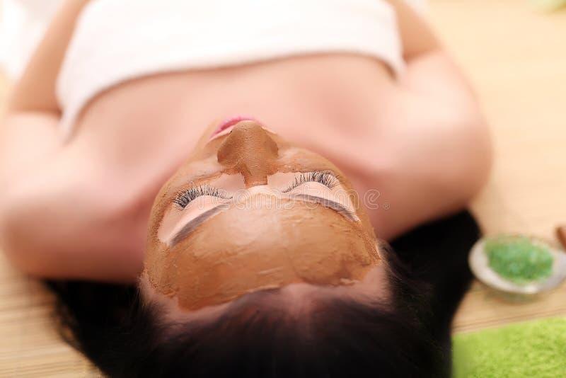 Терапия курорта для молодой женщины имея лицевую маску на салоне красоты - внутри помещения стоковые фотографии rf