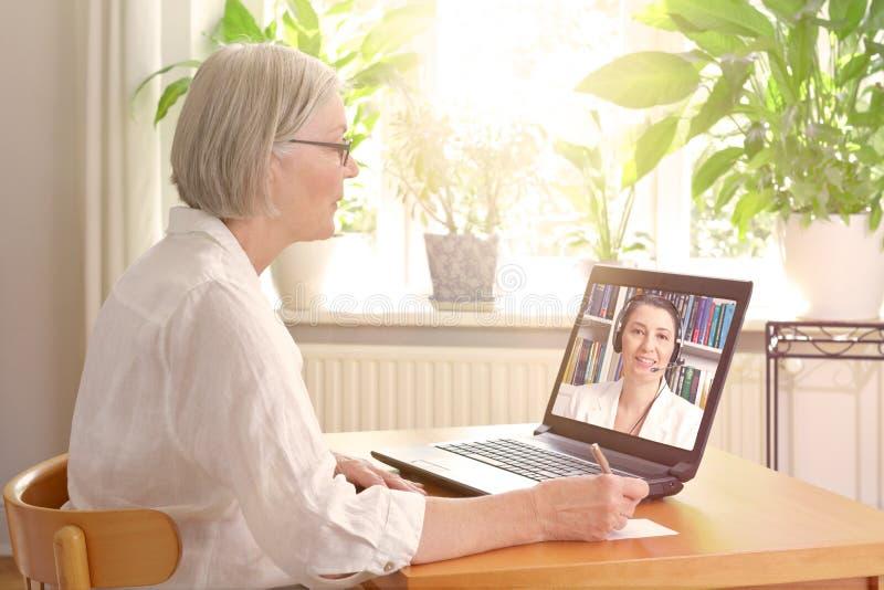 Терапия старшей компьтер-книжки женщины онлайн стоковое фото