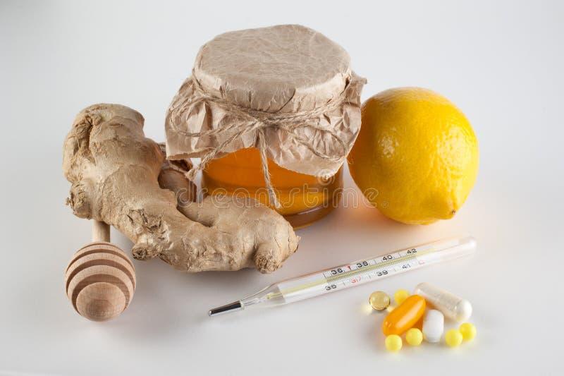 Термометр, пилюльки и витамины ПРОТИВ опарника меда, имбиря, лимона стоковая фотография rf