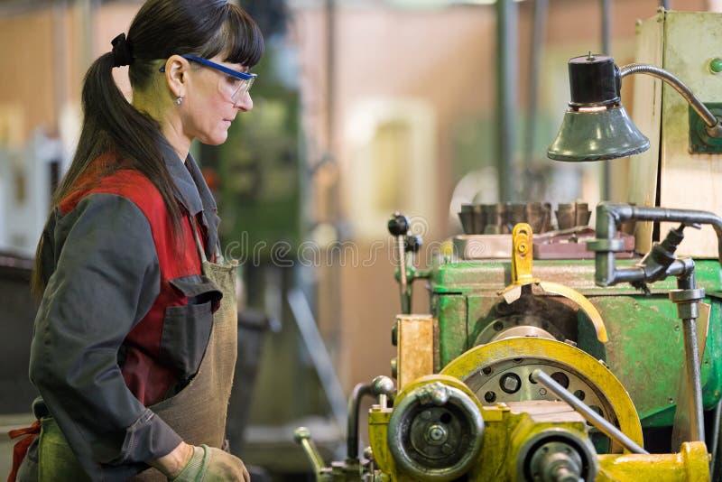 Тернер женщины фабрики работая на машине токарного станка мастерской стоковое фото rf