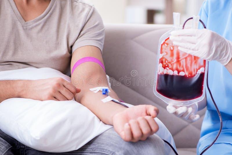 Терпеливое получая переливание крови в клинике больницы стоковая фотография