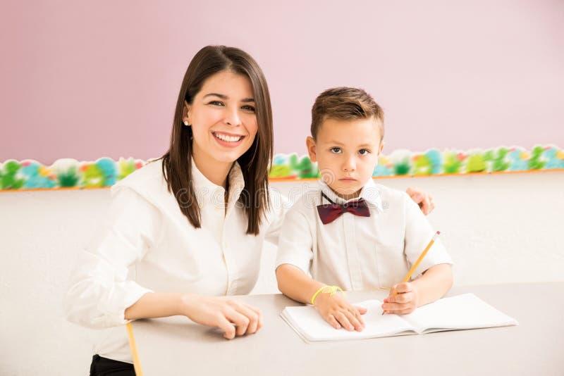 Терпеливый учитель помогая студенту в классе стоковое фото