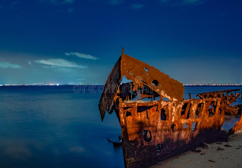 Терпетьый кораблекрушение на пляже на ноче стоковая фотография