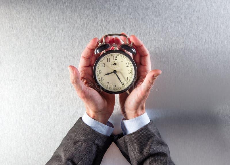 Терпеливый бизнесмен вручает держать будильник для контроля времени стоковые фотографии rf