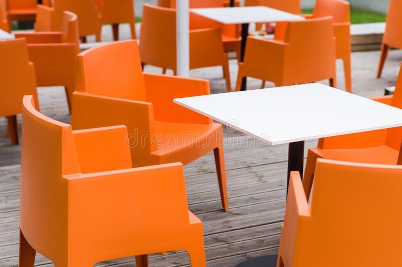 Терраса кафа современной мебели внешняя с оранжевыми стульями стоковые изображения