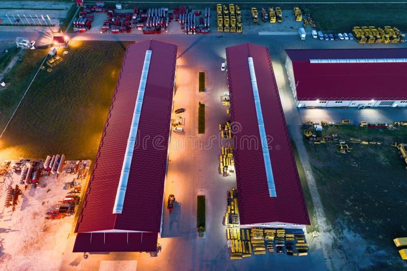 Территория промышленного предприятия Большие ангары с красной крышей Вид с воздуха, стрельба ночи стоковая фотография