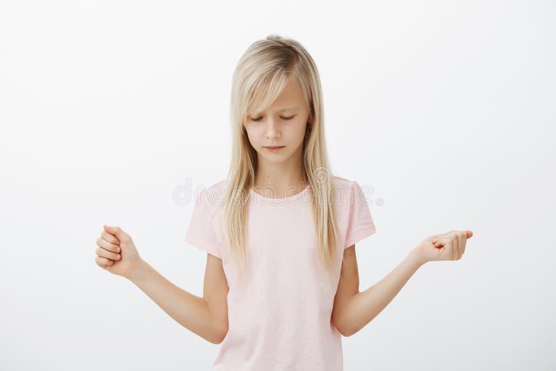 Терять всегда неприятное Портрет девушки хмурой осадки маленькой белокурой, обхватывая кулаков и смотреть вниз, чувствуя тоскливо стоковое фото rf