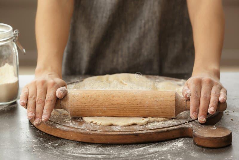 Тесто женщины свертывая на кухонном столе, крупном плане стоковое фото