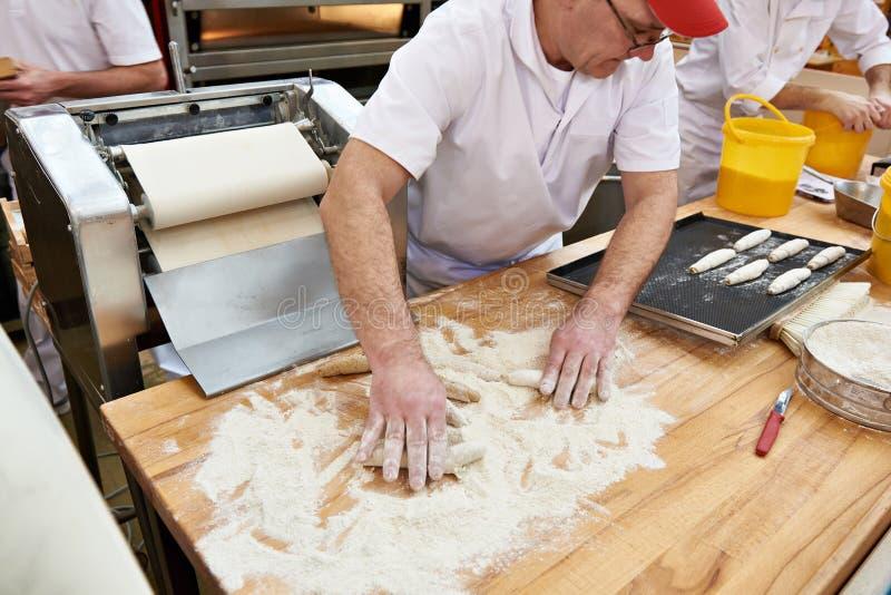 Тесто кашевара хлебопеков для плюшек крена стоковая фотография