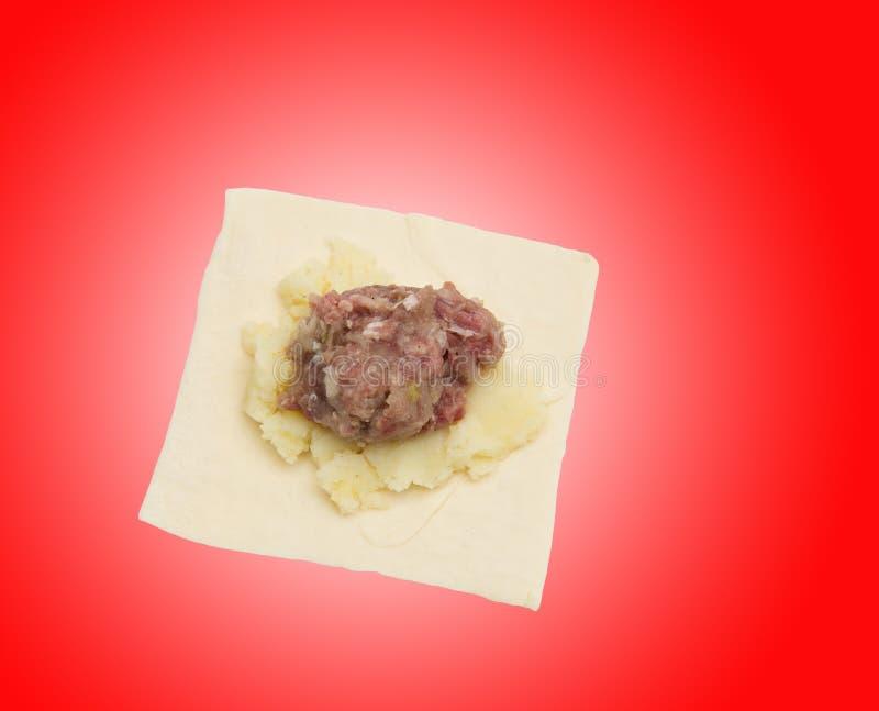Тесто с мясом на красной предпосылке стоковая фотография