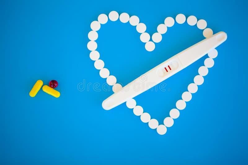 Тест на беременность результат положителен с 2 прокладками Обработка неплодородности с пилюльками, помощи в понимать ребенка стоковое изображение rf