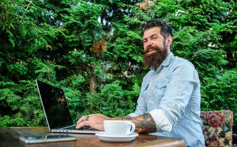 Тетрадь блога работы фрилансера битника онлайн Блоггер создает столб пока насладитесь кофе Бизнесмен человека бородатый сидит стоковые фотографии rf