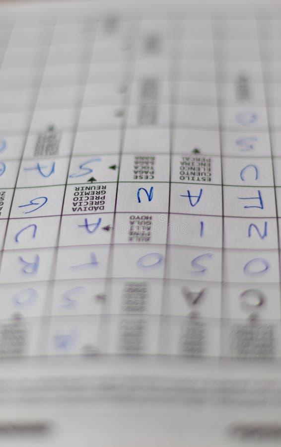 Тетрадь головоломки кроссвордов с письмами и определениями стоковое фото