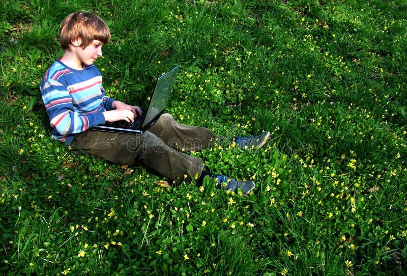 тетрадь зеленого цвета травы ребенка браузера сидит стоковое изображение rf