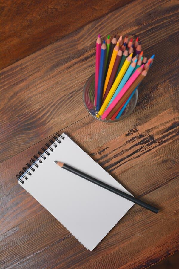 Тетрадь и покрашенные карандаши на деревянной предпосылке стоковое фото rf