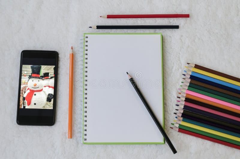 Тетрадь, карандаши цвета для рисовать и телефон стоковая фотография