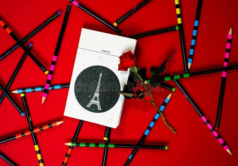 Тетрадь Париж плана взгляда сверху и красная роза на красной предпосылке с красочными карандашами офиса Концепция карты дня Вален стоковые изображения