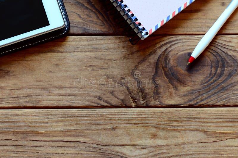 Тетрадь, ПК таблетки, ручка на таблице офиса Деревянная предпосылка с космосом экземпляра для текста workspace Взгляд сверху стоковое изображение rf