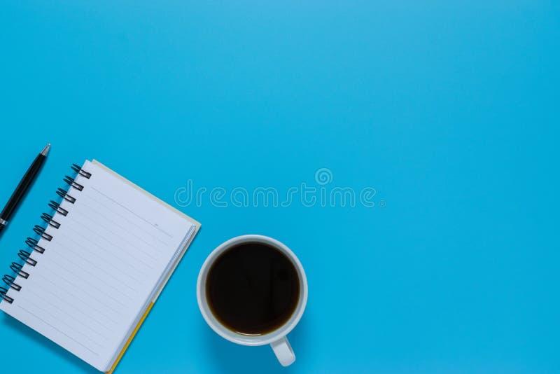 Тетрадь, ручка, или объект взгляда сверху для концепции канцелярские товара на голубой предпосылке стоковые изображения rf