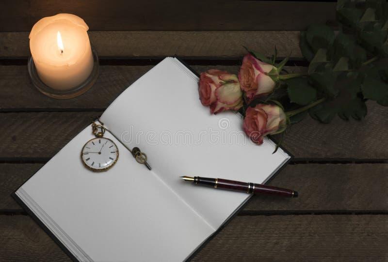 Тетрадь, ручка, розы свечи на темной предпосылке стоковое фото rf