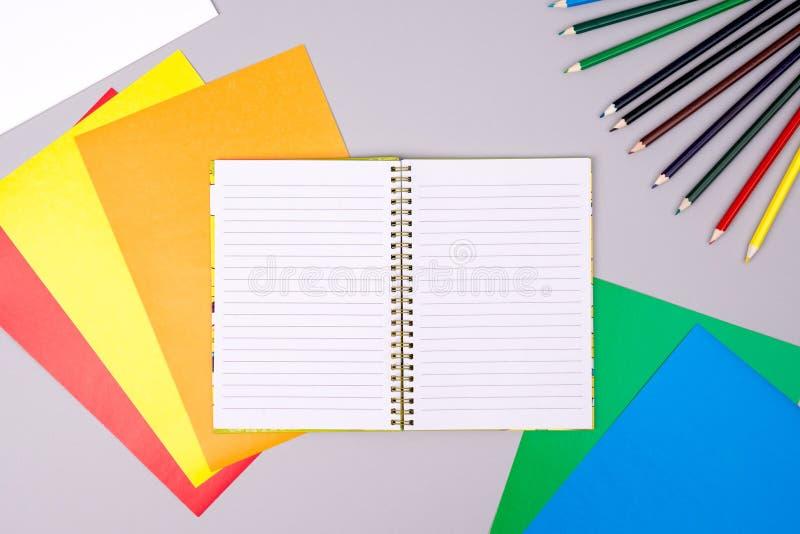 Тетрадь с карандашами цвета и покрашенной бумагой на серой предпосылке стоковое изображение rf