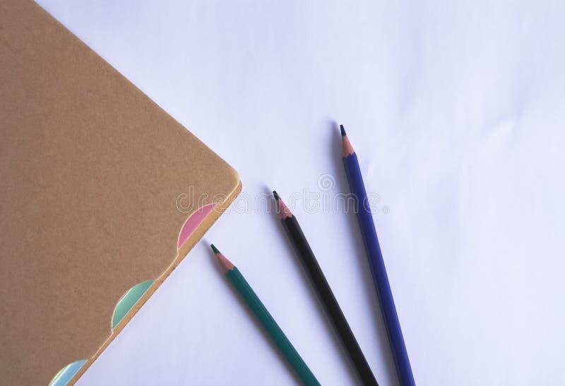 Тетрадь с карандашами стоковая фотография rf