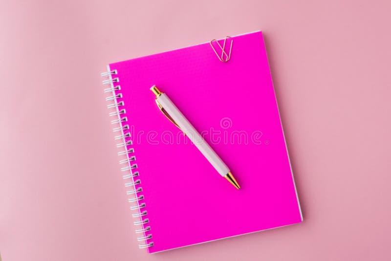 Тетрадь с пластиковой розовой крышкой цвета, ручкой и бумажными зажимами Комплект женщины Розовая предпосылка Селективный фокус стоковая фотография rf
